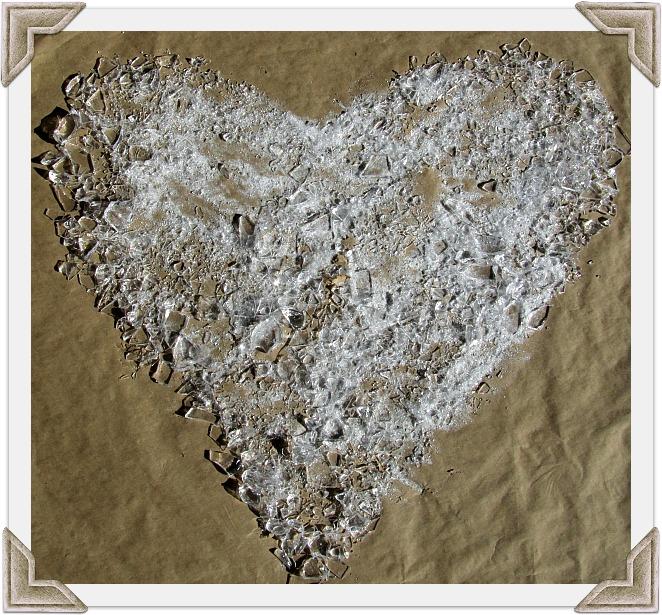 glass heart on beach sand